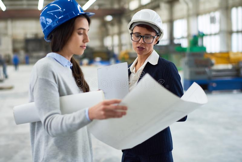 Female Boss Giving Instructions at Factory. Portrait two female engineers wearing hardhats examining work plans in workshop of modern factory, copy space stock photography