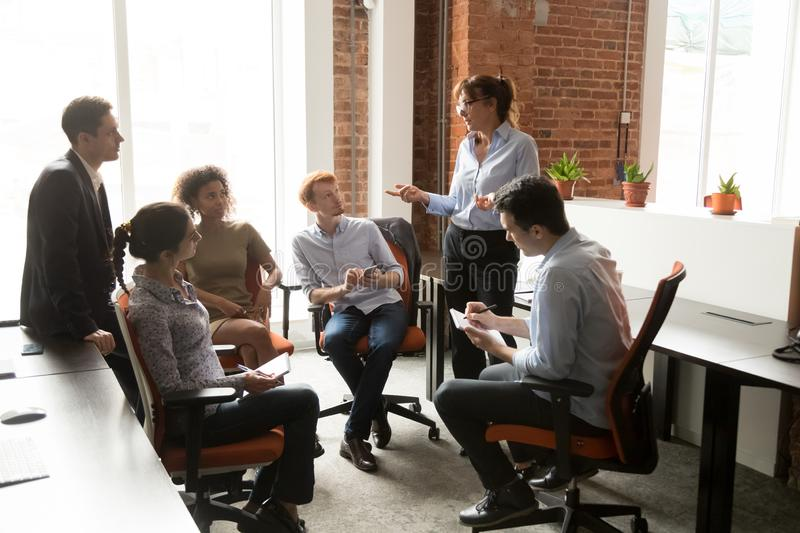 Female boss hold casual meeting brainstorming with employees stock photo