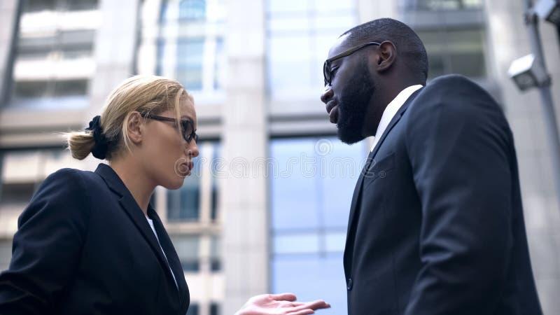 Female boss scolding subordinate, employee justifying himself, business ethics stock photography
