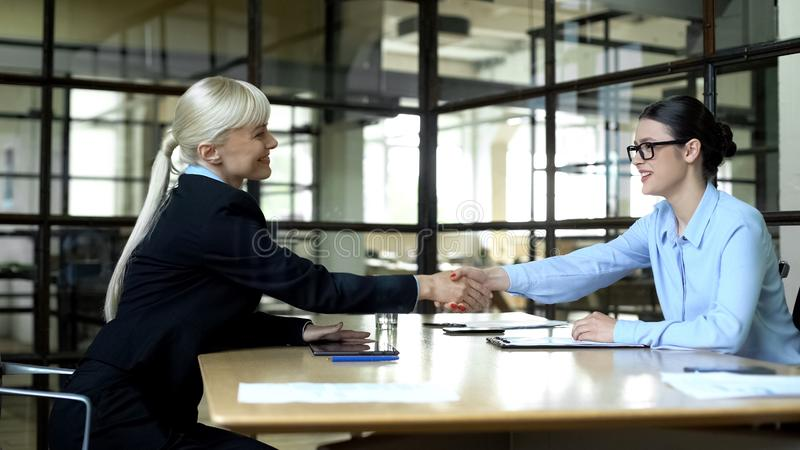 Female boss shaking hand of young manager approving business deal, partnership. Stock photo stock photos