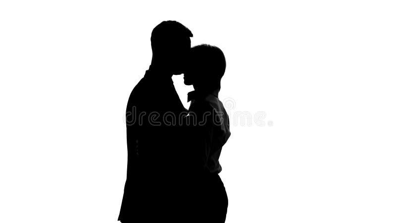 Female boss silhouette tenderly hugging her male secretary in office, romance stock photos