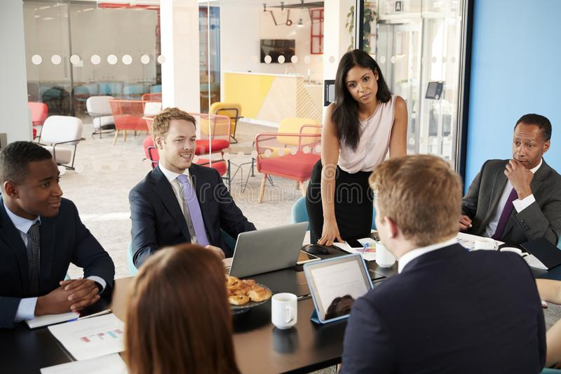 Female boss stands listening to colleagues at team meeting stock photos