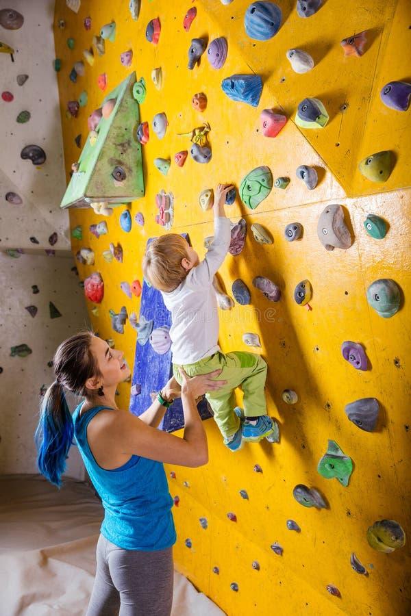 Female bouldering instructor helping boy climb artificial wall. Young female bouldering instructor helping boy climb artificial wall stock photo
