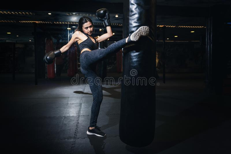Female boxer hitting a huge punching bag at a boxing studio. Woman boxer training hard. Thai boxer punch kick by punching bag, Bl royalty free stock photography