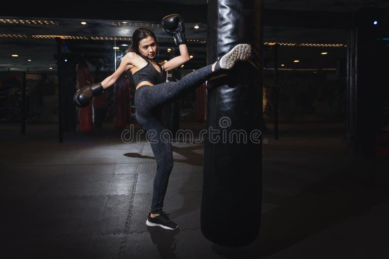 Female boxer hitting a huge punching bag at a boxing studio. Woman boxer training hard. Thai boxer punch kick by punching bag stock image
