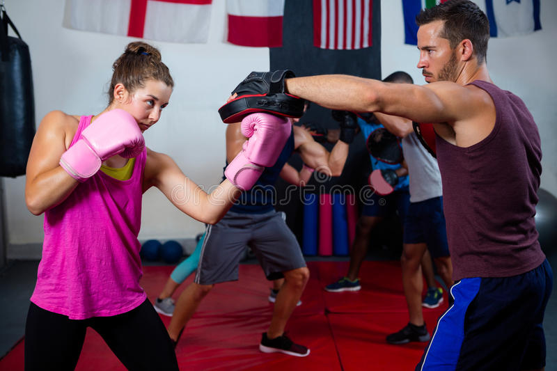 Female boxer and instructor practicing with boxing stock photos