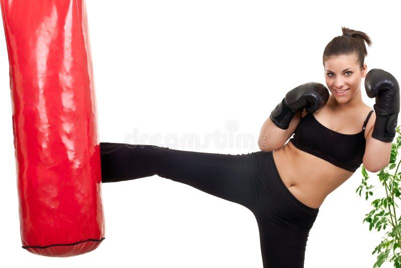 Female boxer kicking punching bag stock images