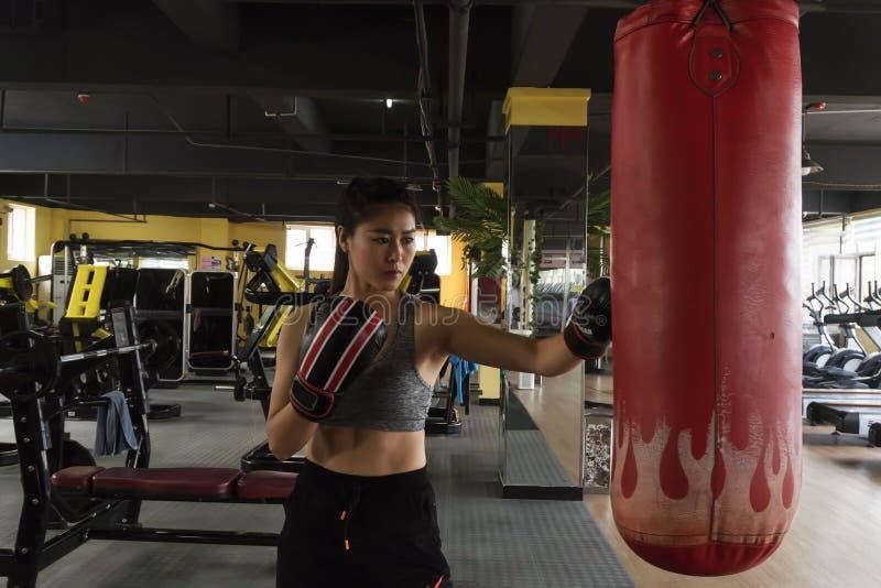 A woman struck sandbags at the gym. royalty free stock photos