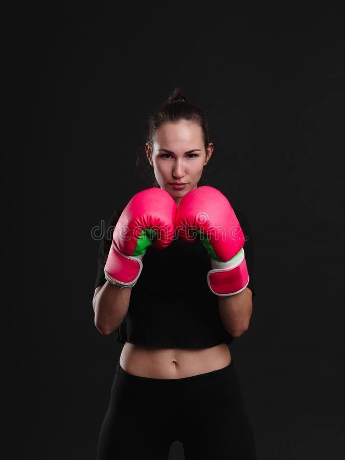 Female boxer posing on black background. Sport concept. Sporty healthy girl boxing at the camera in the studio. Sport concept stock image