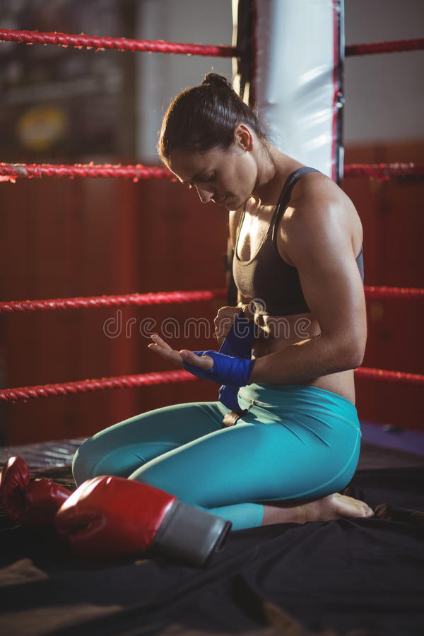 Female boxer wearing blue strap on wrist. In boxing ring royalty free stock photography