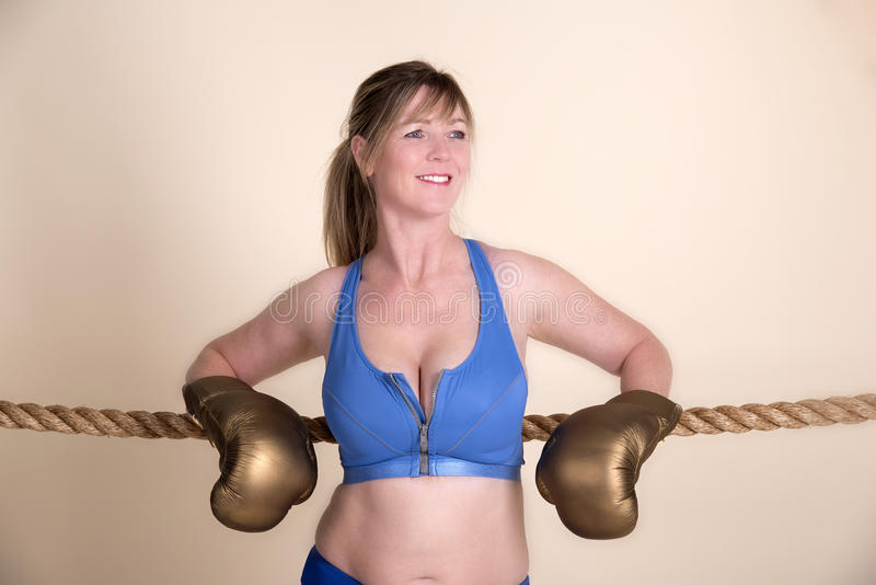 Female boxer wearing golden gloves. Woman boxer wearing golden gloves and a sports bra resting on a rope royalty free stock photo