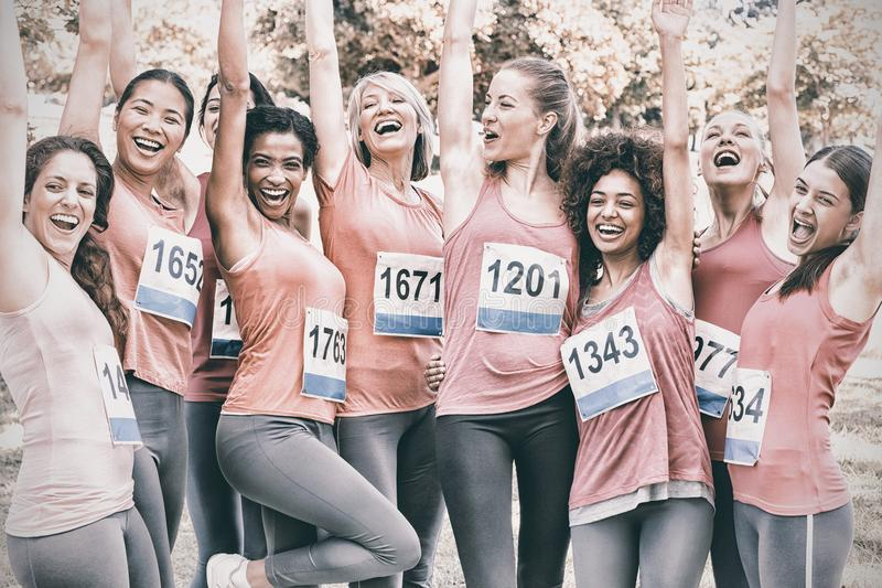 Female breast cancer marathon runners cheering. Excited female breast cancer marathon runners cheering in park royalty free stock photo