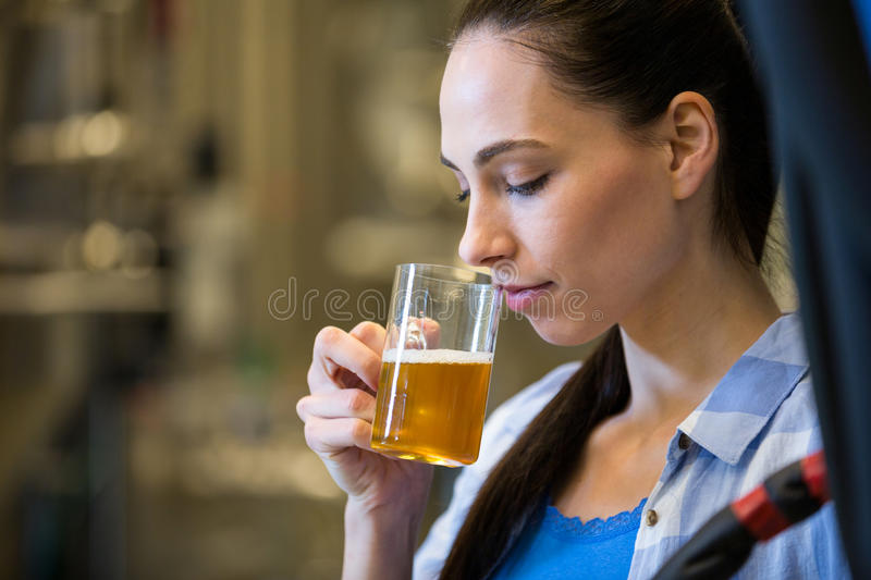 Female brewer testing beer. Close-up of beautiful female brewer testing beer at bewery royalty free stock photo