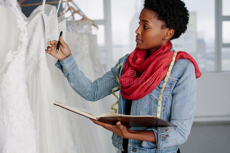 Female bridal store owner looking at wedding gown. With a diary in hand. Dressmaker with diary examining bridal wear pattern royalty free stock image