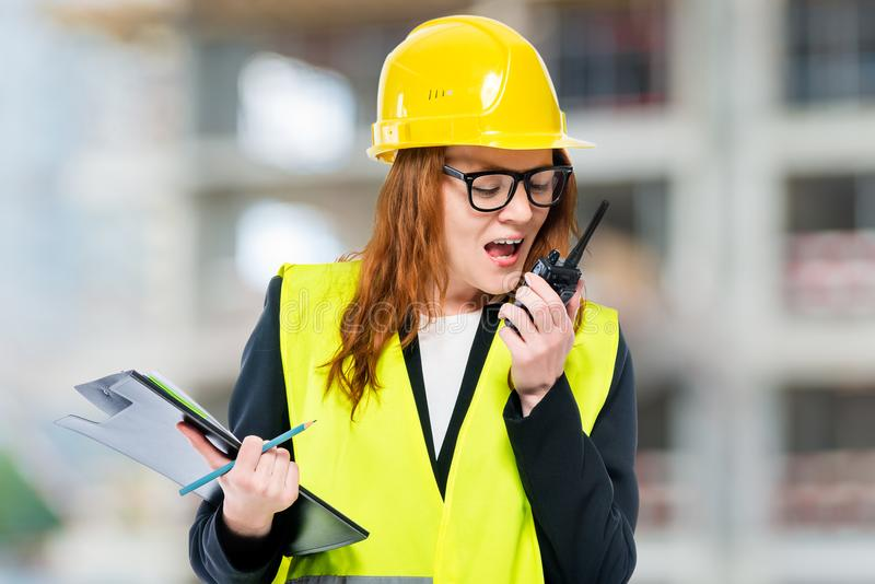 Female brigadier wearing helmet and waistcoat with walkie-talkie at construction site royalty free stock photo