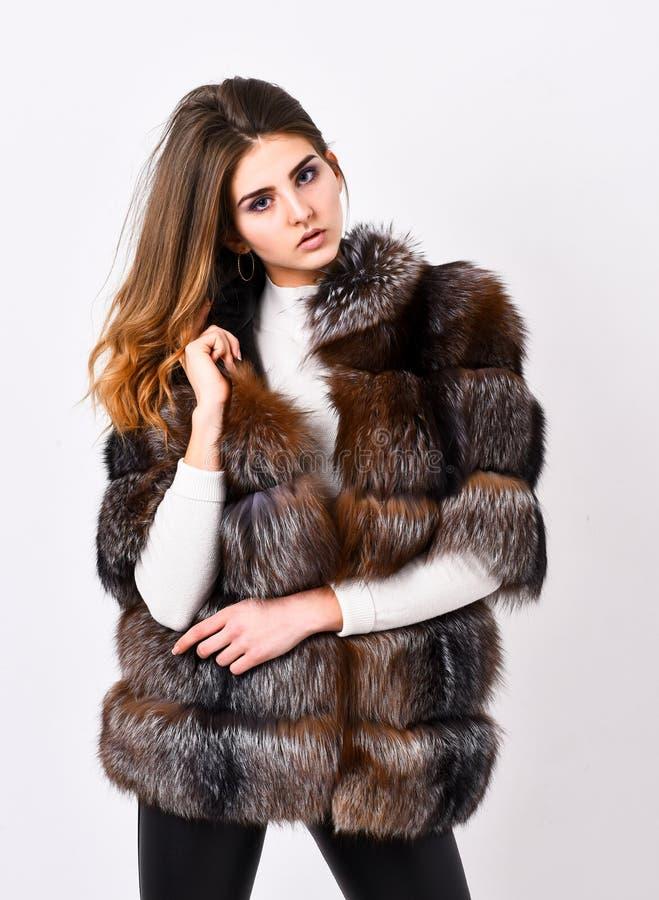 Female brown fur coat. Fur store model posing in soft fluffy warm coat. Pretty fashionista. Fur fashion concept. Woman stock photography