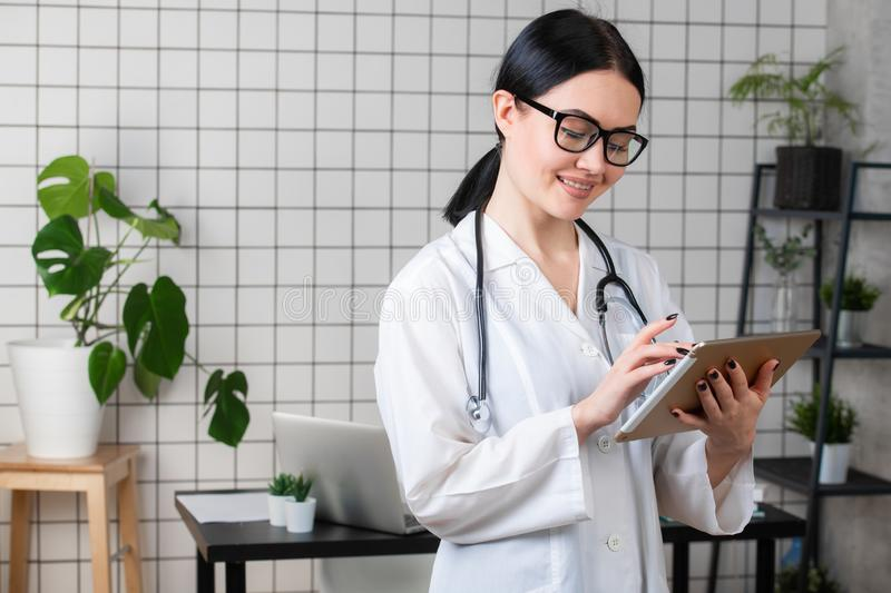 Female brunette doctor wears glasses using tablet, intelligent and lovely woman with the gadget and stethoscope in the. White office background stock image