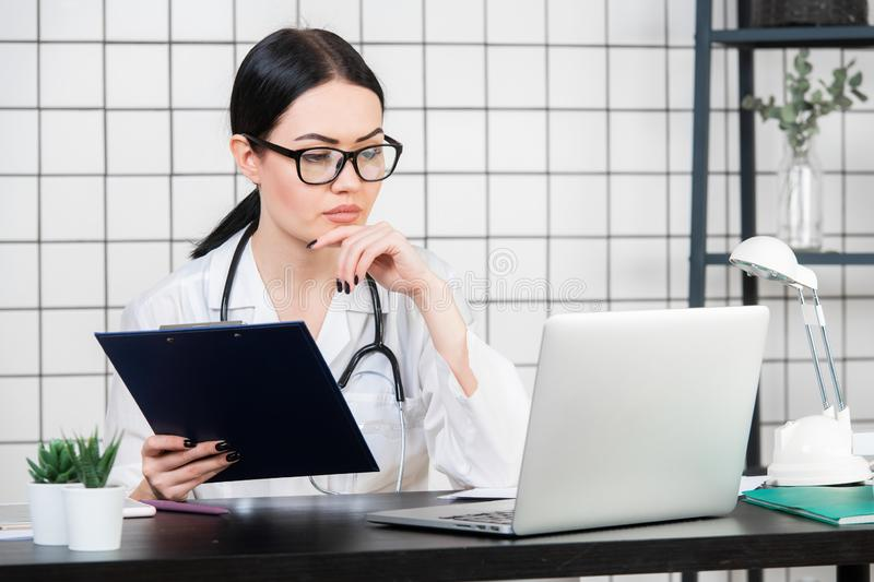 Female brunette doctor wears glasses using tablet, intelligent and lovely woman with the gadget and stethoscope in the. White office background royalty free stock photos