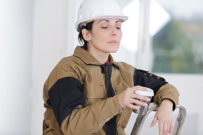 Female builder on break enjoying coffee stock images