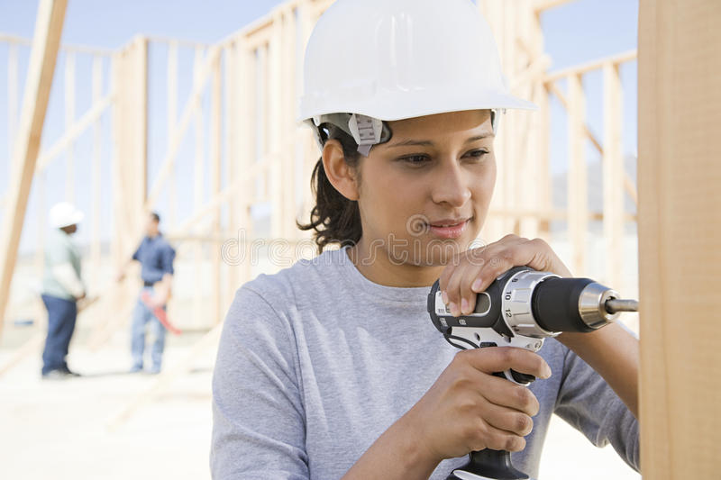 A female builder drilling royalty free stock images