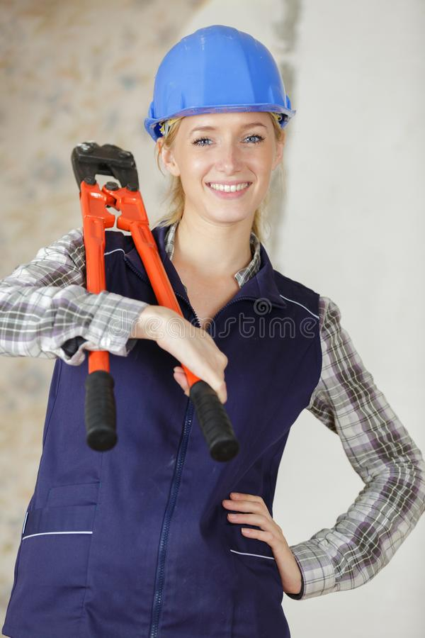 Female builder happily holding shears stock photos