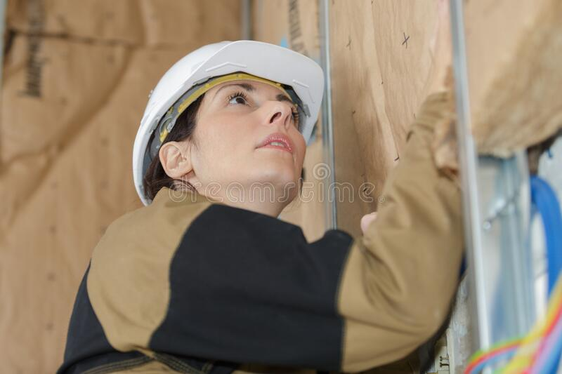 Female builder putting insulation wall stock images