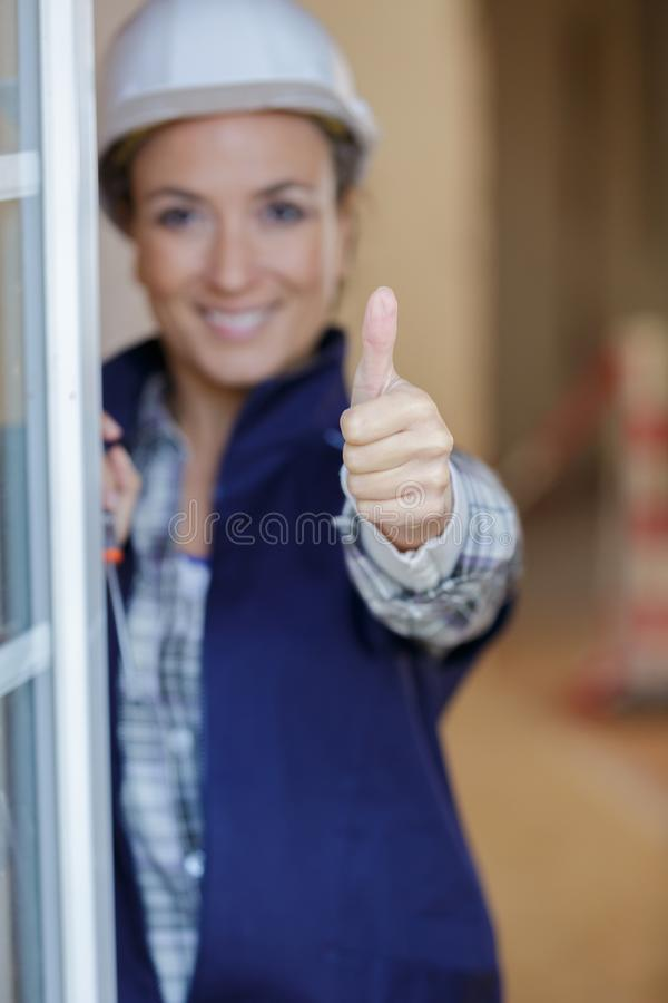Female builder shows thumb up stock photo