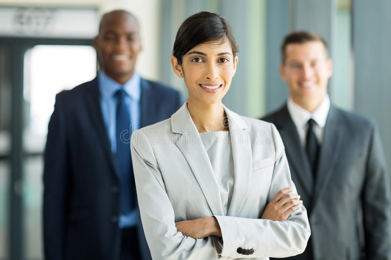 Female business leader with team. Beautiful female business leader with team standing on background royalty free stock photography