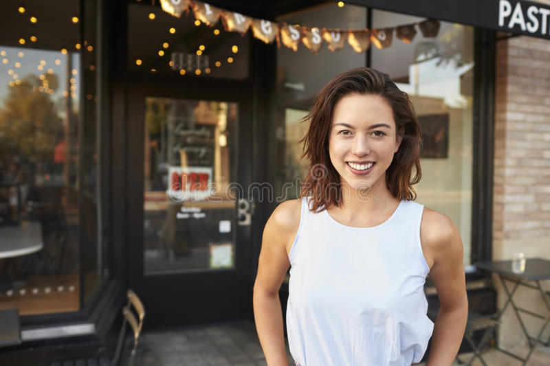 Female business owner standing in the street outside cafe stock photo