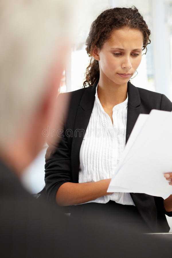 Female business women holding a job interview. Looking at CV royalty free stock images