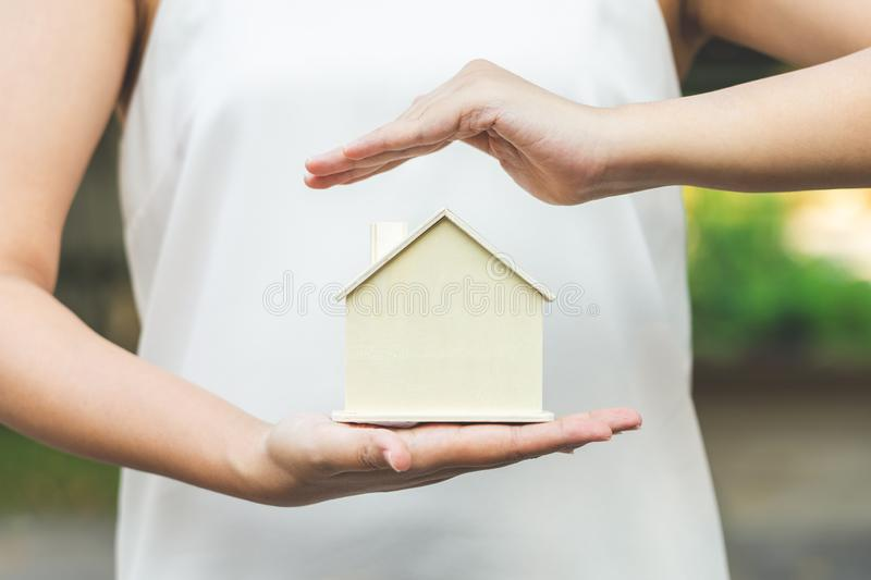 Female businessmen put the model home on the palm. And the hands were covered over the model house roof Media coverage of stock photos