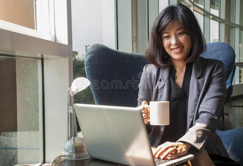 Female businessmen are working on computers and drinking coffee in the office. A female businessman is smiling while working with a computer and using the right royalty free stock images