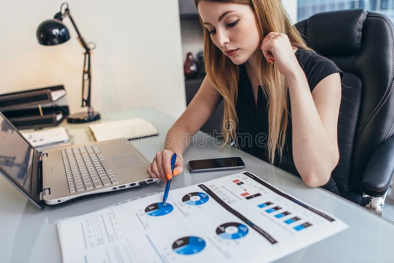 Female businesswoman readind financial report analyzing statistics pointing at pie chart working at her desk stock image