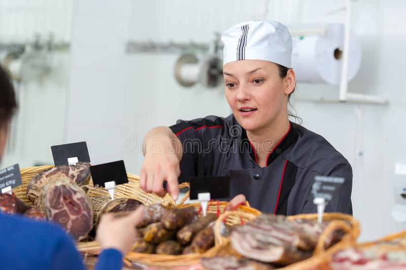 Female butcher serving dried sausage royalty free stock image