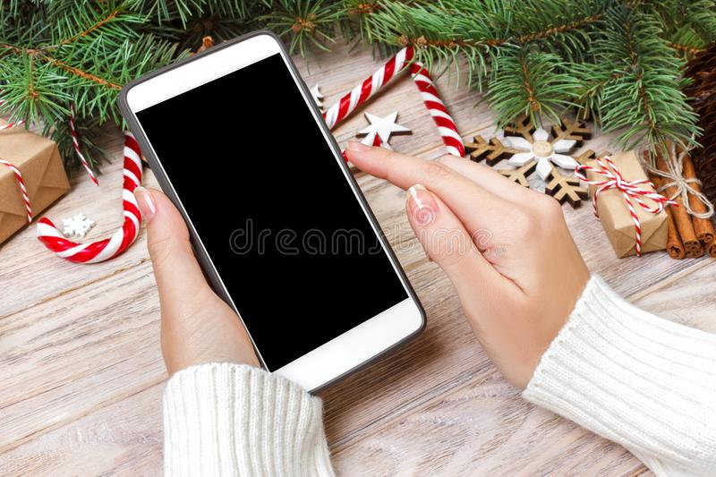 Female buyer makes order at screen of smartphone with copy space. Winter holidays sales. Christmas online shopping stock image