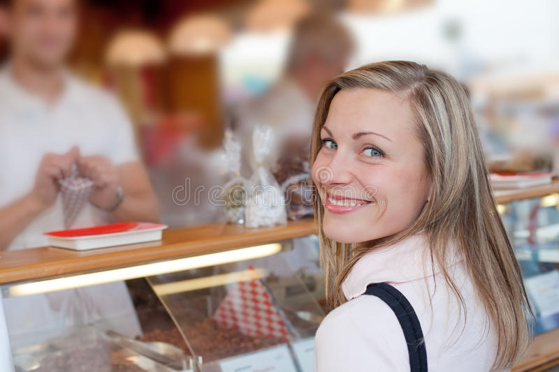 Female buying sweets at the octoberfest. Nice blonde female smiling while buying some roasted nuts at the octoberfest royalty free stock images