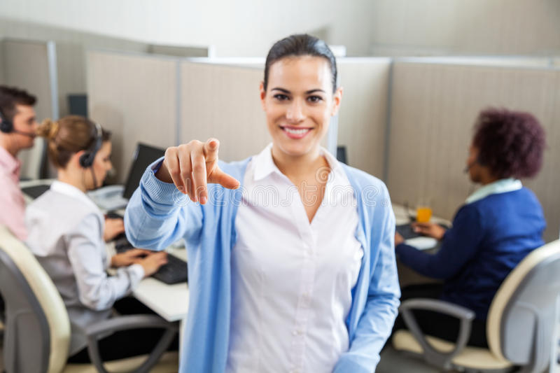 Female Call Center Employee Pointing In Office stock images