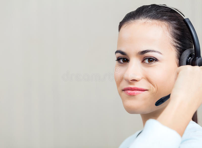 Female Call Center Employee Using Headset. Portrait of smiling female call center employee using headset at office royalty free stock photos