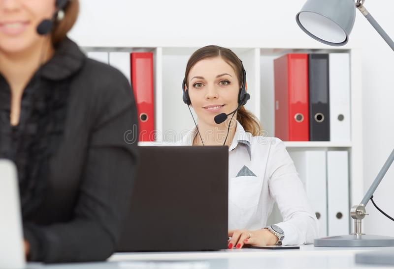 Portrait of smiling pretty female help desk employee with headset at workplace. stock image