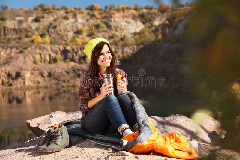 Female camper with thermos sitting on sleeping bag. In wilderness stock images