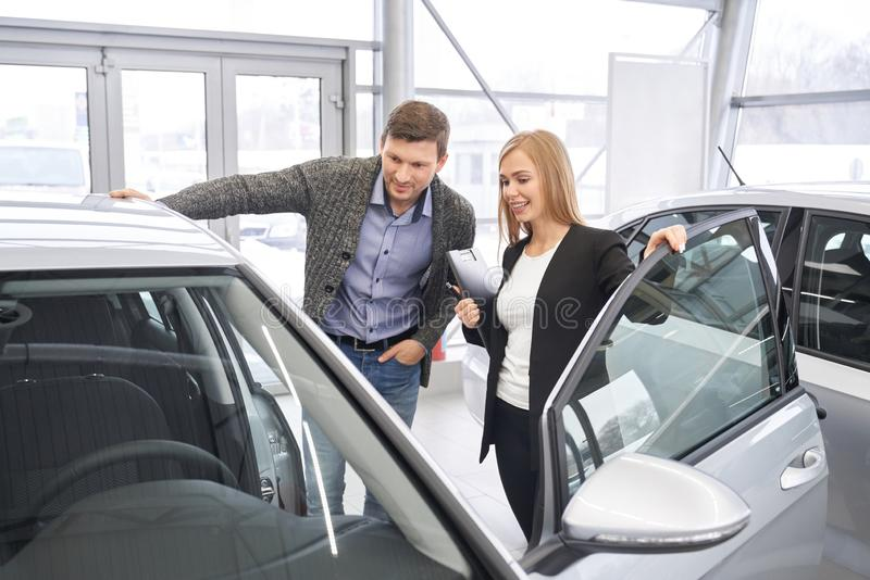 Female car dealer showing automobile to potential buyer. stock images