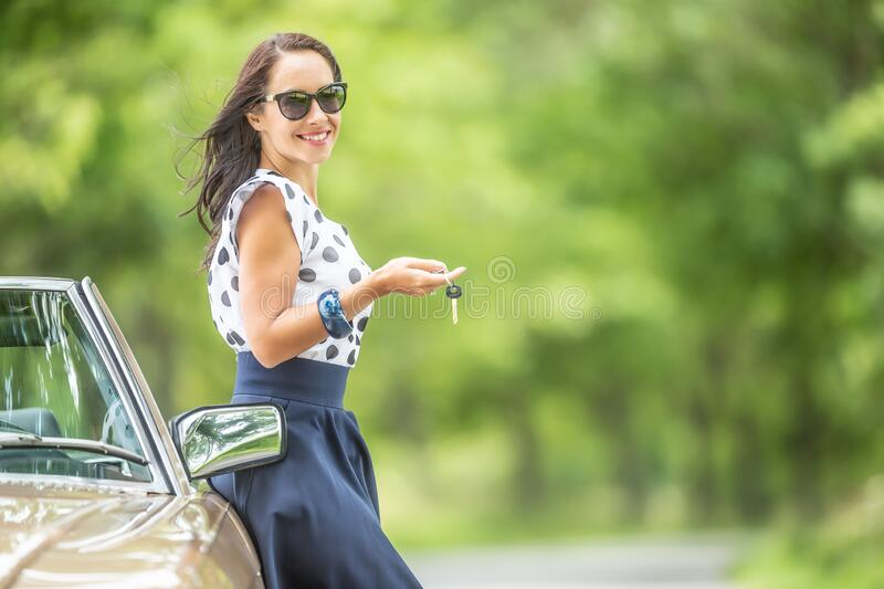 Female with car keys in her hand leans against a vintage convertible parked in the nature royalty free stock images