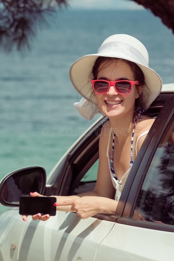 Female in car showing blank screen smartphone display. Travel an stock photo