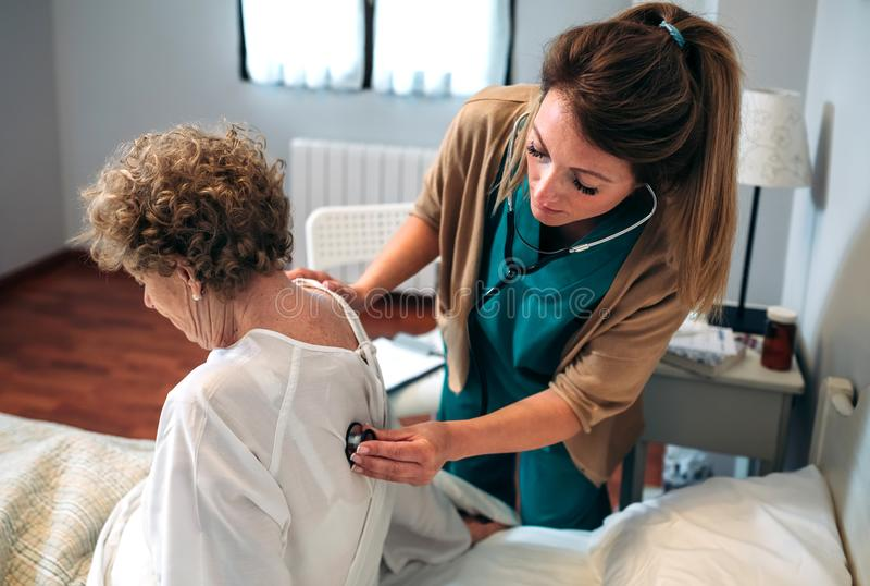 Caregiver auscultating senior woman. Female caregiver auscultating senior women at home stock images