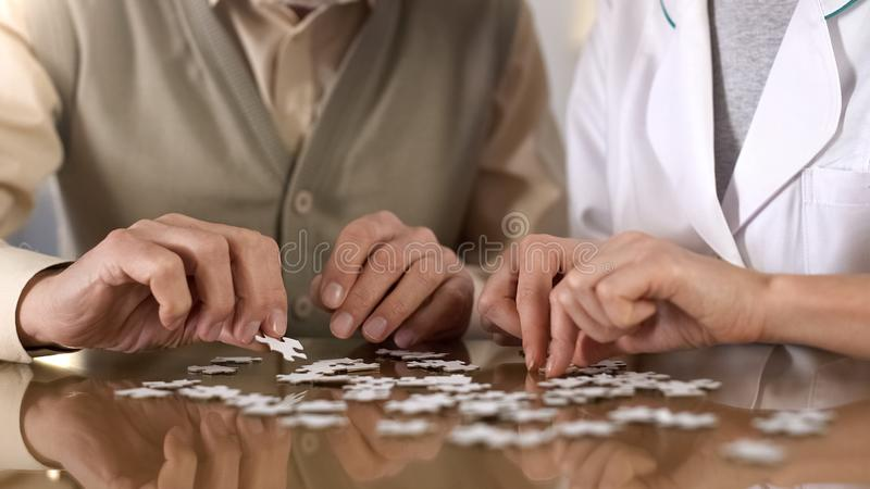 Female caregiver helping aged man doing puzzle table, mental training, alzheimer royalty free stock photography