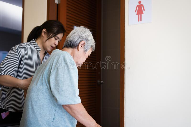 Female caregiver is helping support elderly woman walk into the restroom carefully,asian senior with bladder control problem need royalty free stock photography