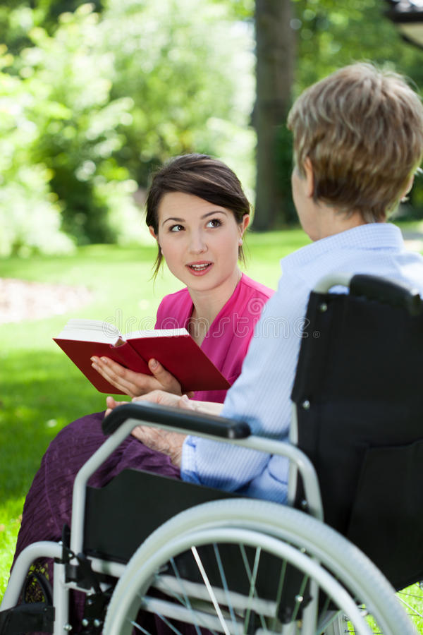 Female caregiver reading book with senior woman. Female caregiver reading book with senior women at garden royalty free stock image