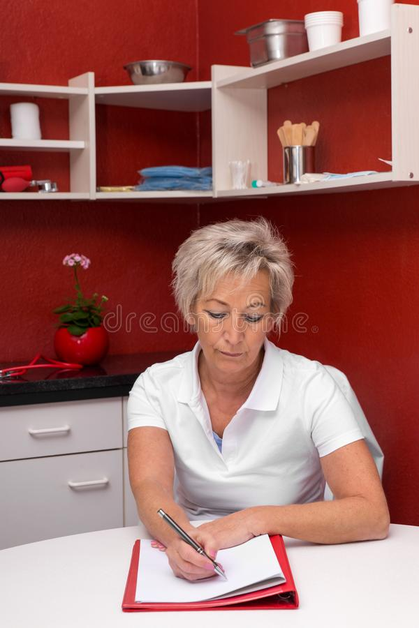 Female caregiver in an red office. Is writing an anamnesis, clipboard in front of her on a table stock photos