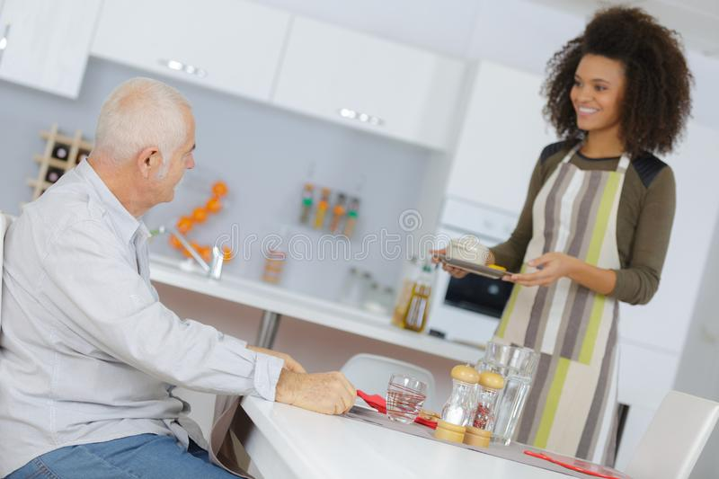 Female carer assisting and supporting senior man royalty free stock photo