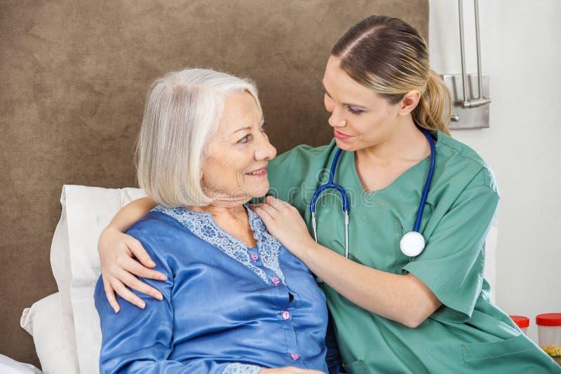 Female Caretaker Comforting Senior Woman stock photo